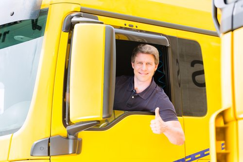 truck driver in driver's seat with thumb up